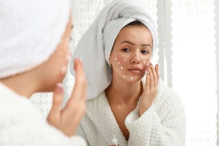 Ragazza teenager con problemi di acne che applica crema vicino allo specchio in bagno