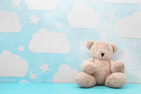 Teddy bear on wooden table near wall with blue sky, space for text. Baby room interior Banque d'images