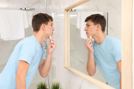 Tienerjongen met acneprobleem die crème aanbrengt in de buurt van de spiegel in de badkamer