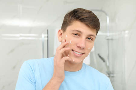Teen guy with acne problem applying cream in bathroom