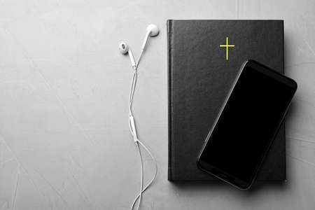 Bible, phone and earphones on light grey background, flat lay with space for text. Religious audiobook