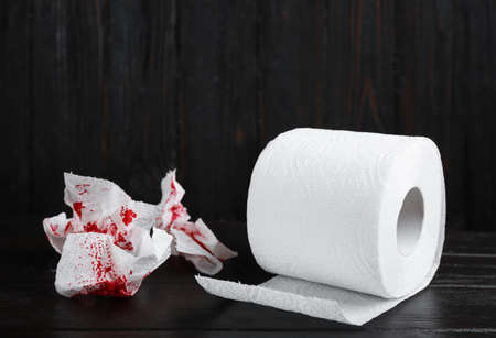 Toilet paper with blood on black wooden table. Hemorrhoid problems