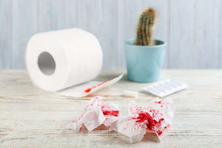 Sheets of toilet paper with blood on white wooden table. Hemorrhoid problems