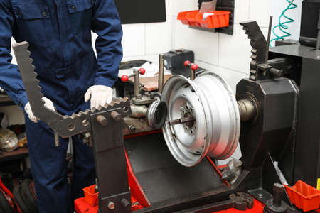 Man working with car disk lathe machine at tire service, closeup