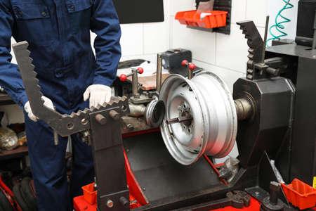Mann, der mit Autoscheibendrehmaschine beim Reifenservice arbeitet, Nahaufnahme
