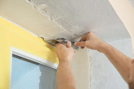 Man plastering window area with putty knife indoors, closeup. Interior repair