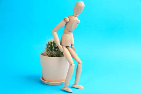 Wooden human figure and cactus on light blue background. Hemorrhoid problems 스톡 콘텐츠