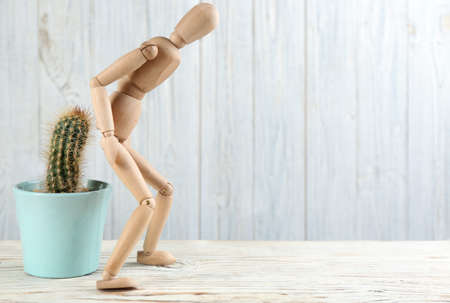 Wooden human figure and cactus on white table, space for text. Hemorrhoid problems 스톡 콘텐츠
