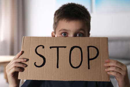 Abused little boy with sign STOP indoors. Domestic violence concept 免版税图像