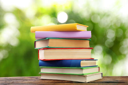 Stack of colorful books on wooden table against blurred green background