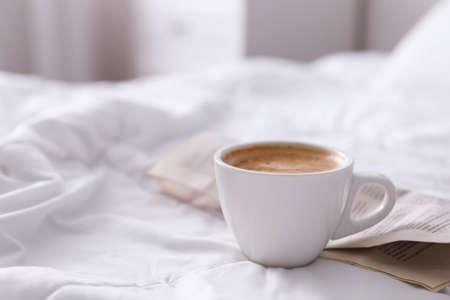 Morgenkaffee und Zeitung auf dem Bett. Platz für Text