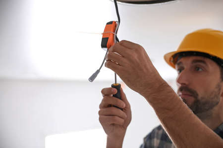 Worker repairing lamp on stretch ceiling indoors. Space for text Stock Photo