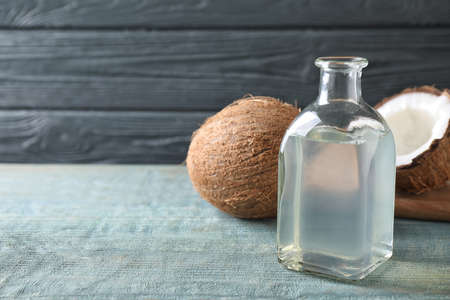 Coconut oil on light blue wooden table, space for text
