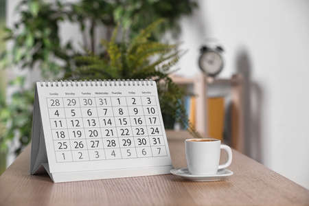 Calendar and cup of coffee on wooden table against blurred background