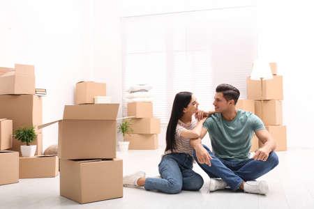 Gelukkig paar in kamer met kartonnen dozen op verhuisdag Stockfoto