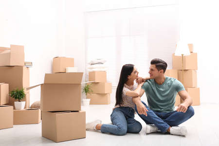 Happy couple in room with cardboard boxes on moving day Stockfoto