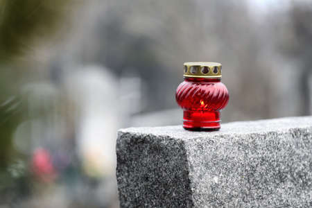 Lamp with candle on grey granite tombstone outdoors, space for text. Funeral ceremony