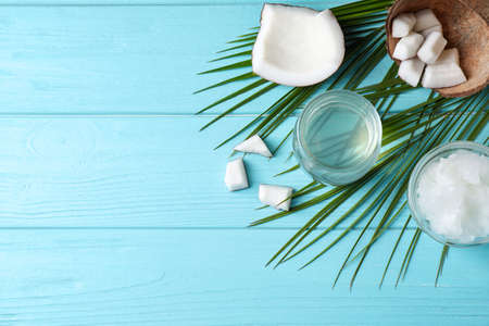 Flat lay composition with coconut oil on light blue wooden table, space for text