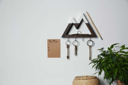 Wooden key holder and to do list on light grey wall indoors. Space for text