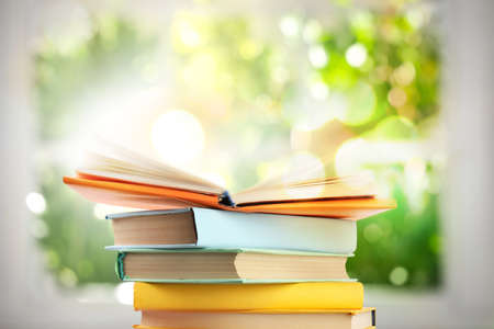 Stack of colorful books on blurred green background