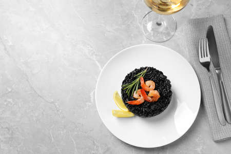 Delicious black risotto with shrimps served on grey marble table, flat lay. Space for text 写真素材