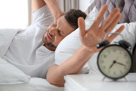 Sleepy man turning off alarm clock at home in morning