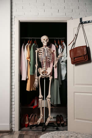 Artificial human skeleton model among clothes in wardrobe room