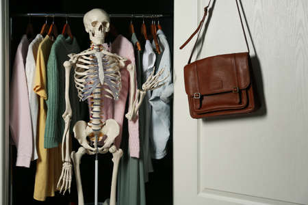 Artificial human skeleton model among clothes in wardrobe
