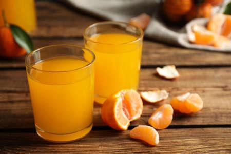 Verres de jus de mandarine frais et fruits sur table en bois Banque d'images