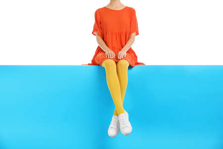 Woman wearing yellow tights and stylish shoes sitting on color background, closeup