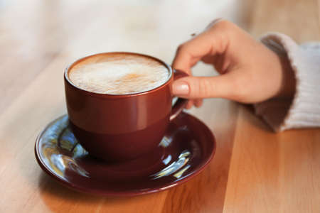 Woman with aromatic coffee at table in cafe, closeup Stock Photo