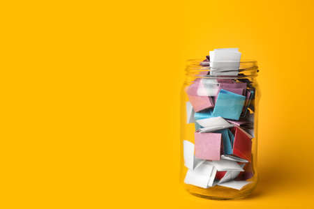 Glass Jar Full Of Folded Paper Sheets On Yellow Background, Space ...