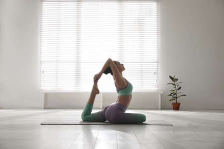 Woman practicing one legged king pigeon asana in yoga studio. Eka pada rajakapotasana pose Banco de Imagens