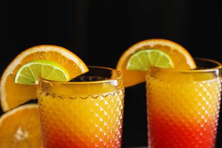 Fresh alcoholic Tequila Sunrise cocktails on dark background, closeup Banque d'images