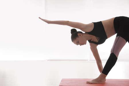 Young woman practicing extended triangle asana in yoga studio. Utthita Trikonasana pose Imagens