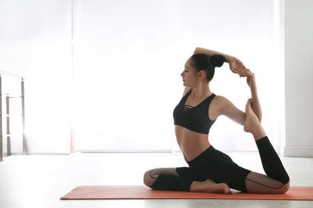 Woman practicing mermaid asana in yoga studio. Eka pada rajakapotasana pose