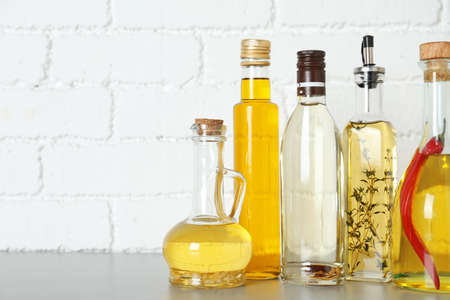 Different cooking oils on grey table. Space for text