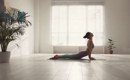 Woman practicing cobra asana in yoga studio. Bhujangasana pose Banco de Imagens