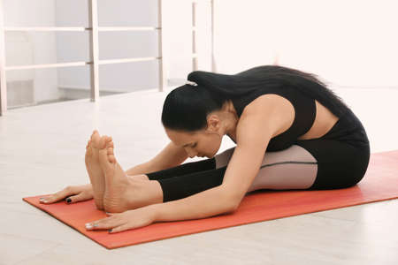 Woman practicing seated forward bend asana in yoga studio. Paschimottanasana pose Banco de Imagens - 150647588