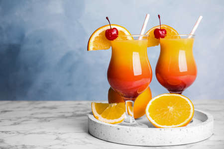 Fresh alcoholic Tequila Sunrise cocktails on marble table Banque d'images