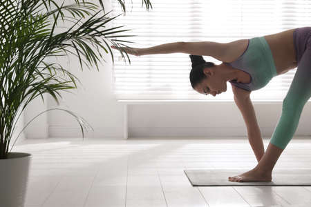 Young woman practicing extended triangle asana in yoga studio. Utthita Trikonasana pose Banco de Imagens