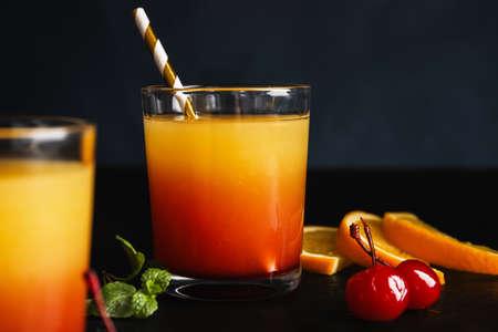Fresh alcoholic Tequila Sunrise cocktail on black table