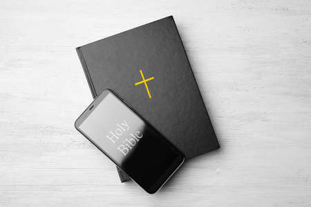 Bible and phone on white wooden background, top view. Religious audiobook