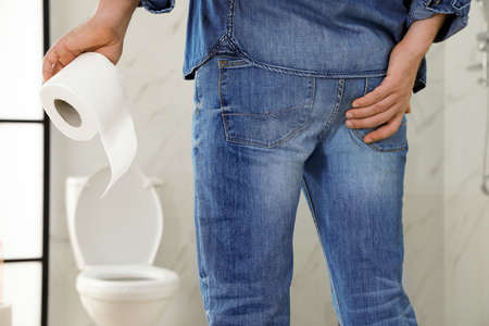 Man with toilet paper suffering from hemorrhoid in rest room, closeup
