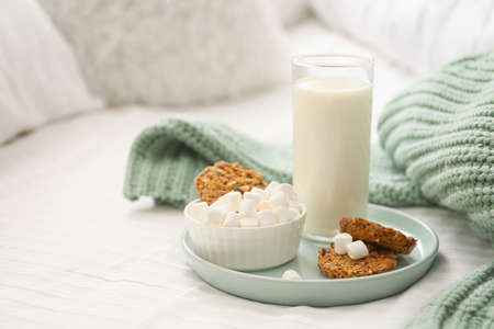 Cookies, marshmallows and milk on bed. Delicious morning meal Stock Photo