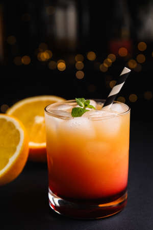 Fresh alcoholic Tequila Sunrise cocktail on grey table