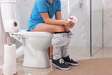 Junge hält Toilettenpapier mit Blutfleck im Ruheraum, Nahaufnahme. Hämorrhoiden-Konzept