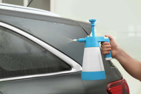 Worker spraying water onto car window before tinting in workshop, closeup