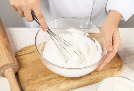 Woman whipping egg whites at wooden table, closeup. Baking pie Archivio Fotografico