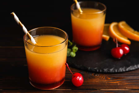 Fresh alcoholic Tequila Sunrise cocktail on wooden table